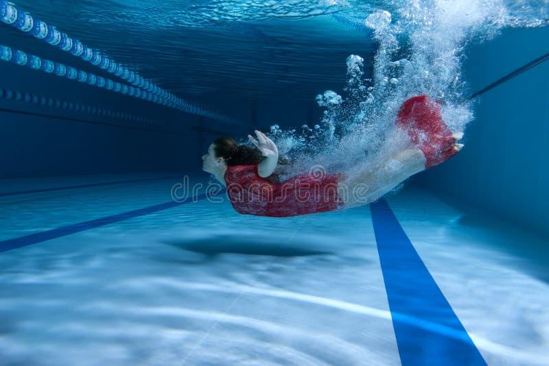 Simmaren i klänningen dyker undervattens- royaltyfria foton