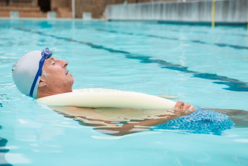 Simning för hög man i pöl arkivbild