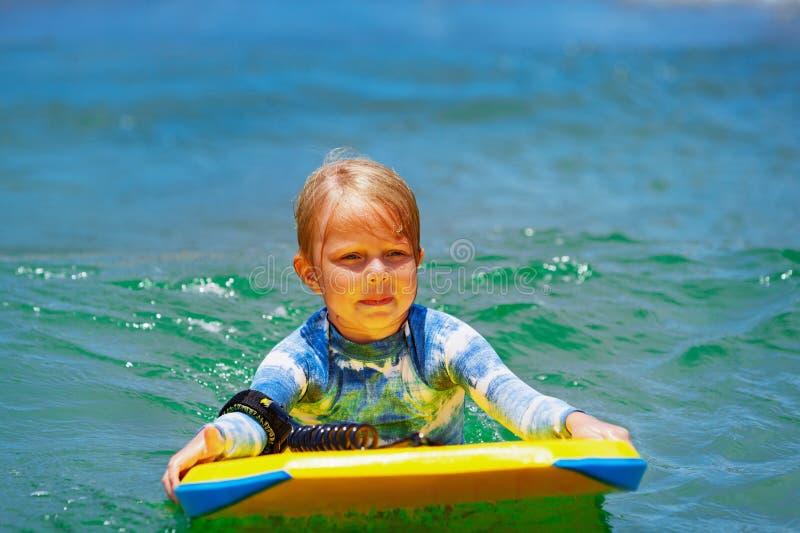 Simning för litet barn med bodyboard på havet vinkar royaltyfri fotografi