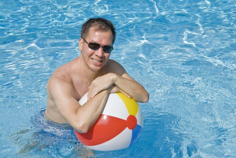 simning för pöl för man för bollstrandholding royaltyfria bilder