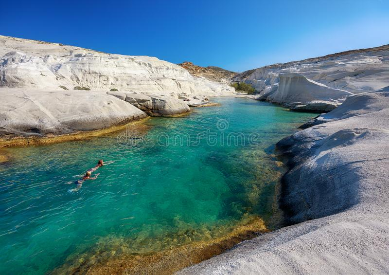 Simning för två kvinnor i klart vatten av den Sarakiniko fjärden, Milos ö, Cyclades royaltyfri bild