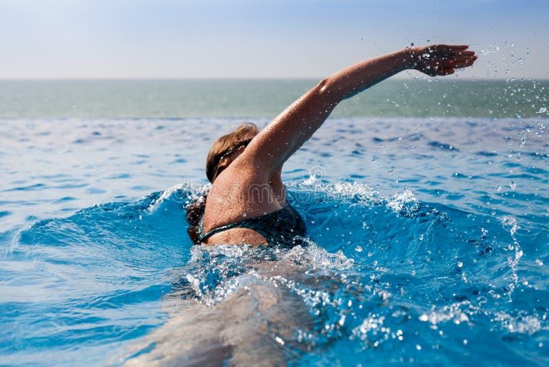 Simning för ung kvinna i en pöl med havsikt royaltyfria foton