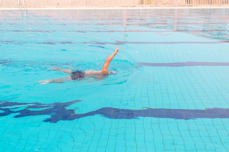Simning för ung man i simbassängen Färdig simmareutbildning i simbassängen royaltyfri fotografi