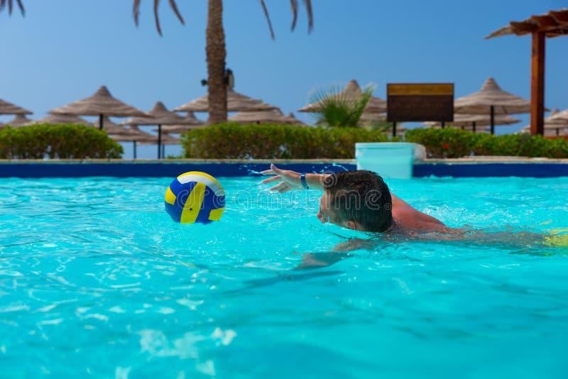 Simning för ung man och försöka att fånga bollen arkivfoton
