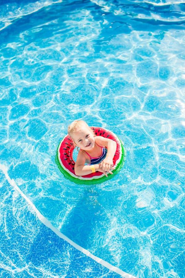 Simning sommarsemester - älskvärd le flicka som spelar i blått vatten med livboj-vattenmelon royaltyfria foton