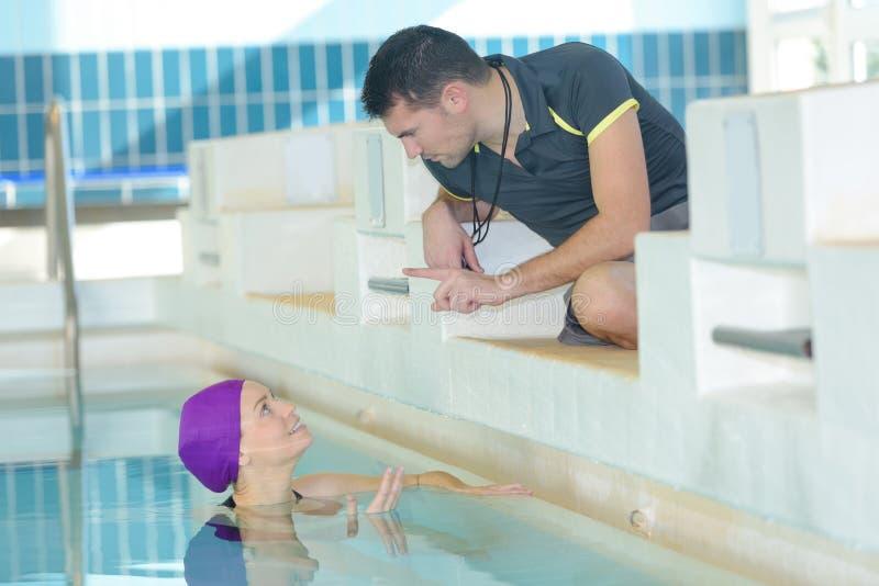 Simninginstruktör som ger rådgivning till idrottsman nen royaltyfri foto