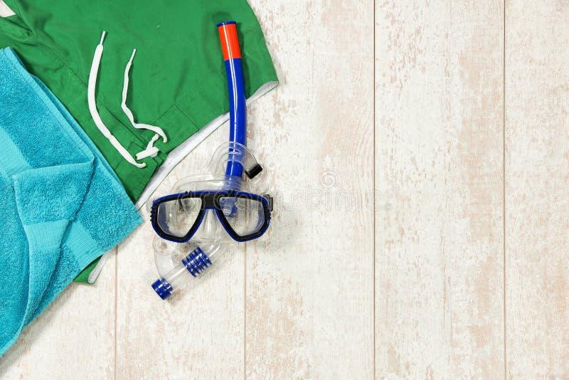 Simningstammar, handduk och snorklamaskering på golvtilja royaltyfria foton