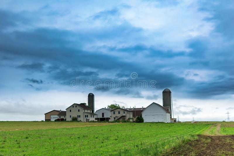 A simple Amish farm house with 2 silos in rural Pennsylvania, Lancaster County, PA, USA royalty free stock photo
