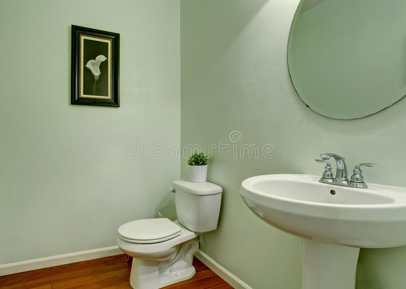 Simple bathroom interior with green walls, white sink and toilet. Also round mirror stock photos