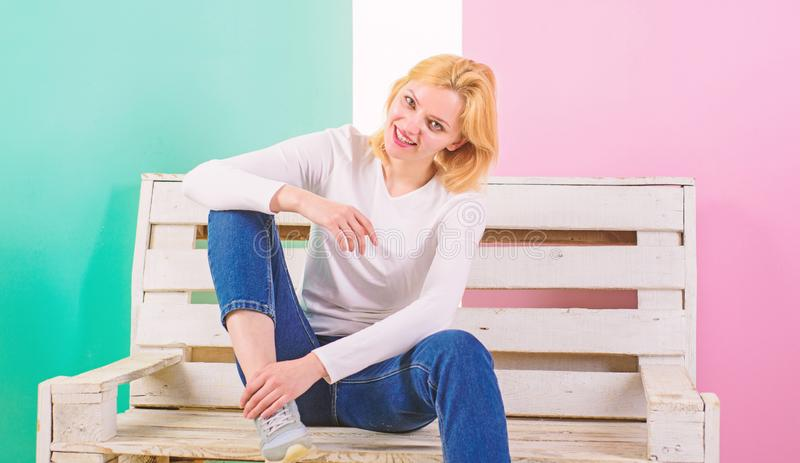 Simple beauty. She is simply gorgeous. Beautiful young woman smile while sitting on bench against pink background. Girl royalty free stock photos
