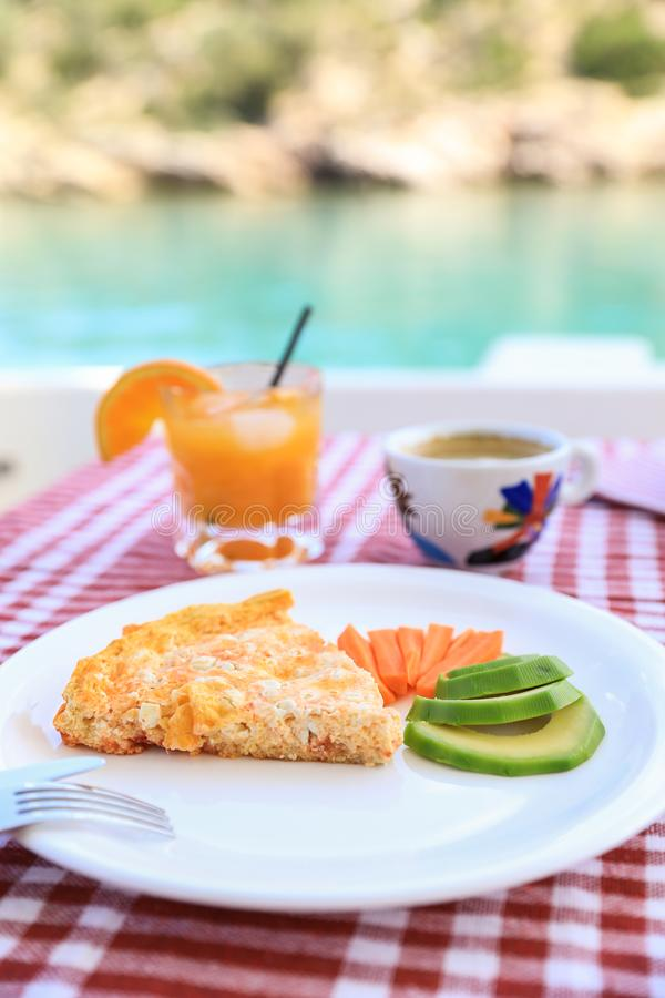 A simple breakfast of omelet, pieces of avocado and carrots, a cup of coffee and a glass of fresh orange juice during a stock photos