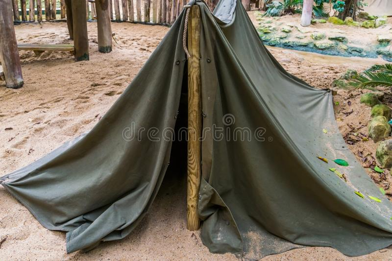 Simple camping tent made out of a wooden pole and a canvas, basic survival equipment. A simple camping tent made out of a wooden pole and a canvas, basic stock photo