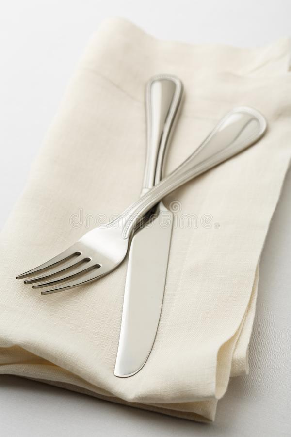 Simple, casual fine dining place setting with high quality silverware fork and knife on white linen napkin with white tablecloth stock photo
