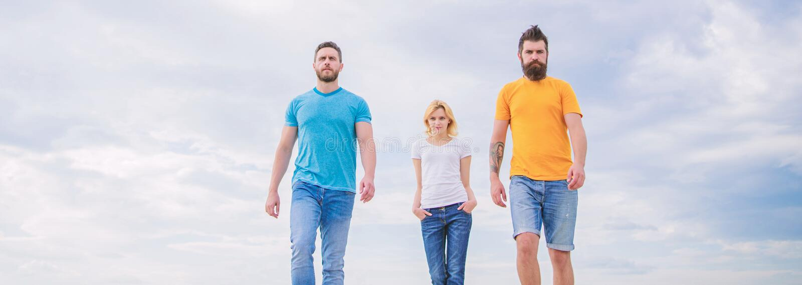 Simple casual must haves. Group of people in casual wear. Pretty woman and men friends walking outdoor. Young people in stock photo