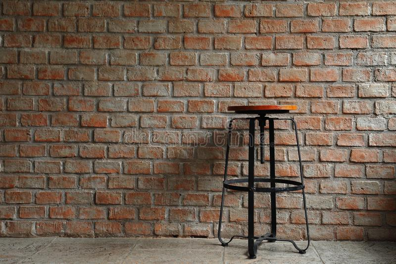 Simple chair with shadow cast on rustic brick and concrete wall pattern for industrial and minimalism design stock photography