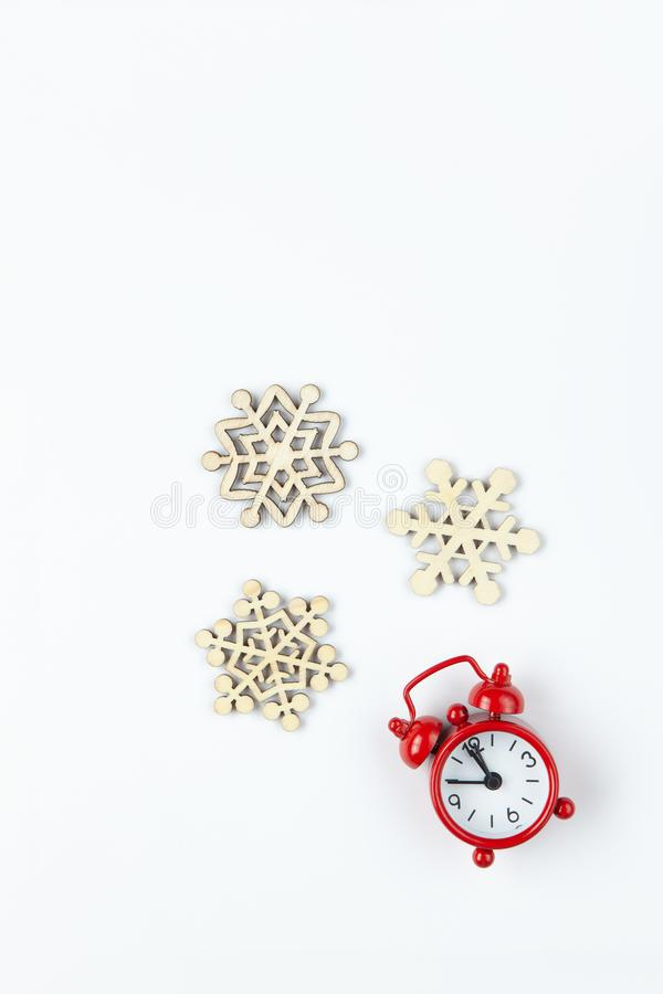 Simple Christmas composition. Small analog red clock, wooden snowflakes on white background. Minimal style flat lay, for social stock image