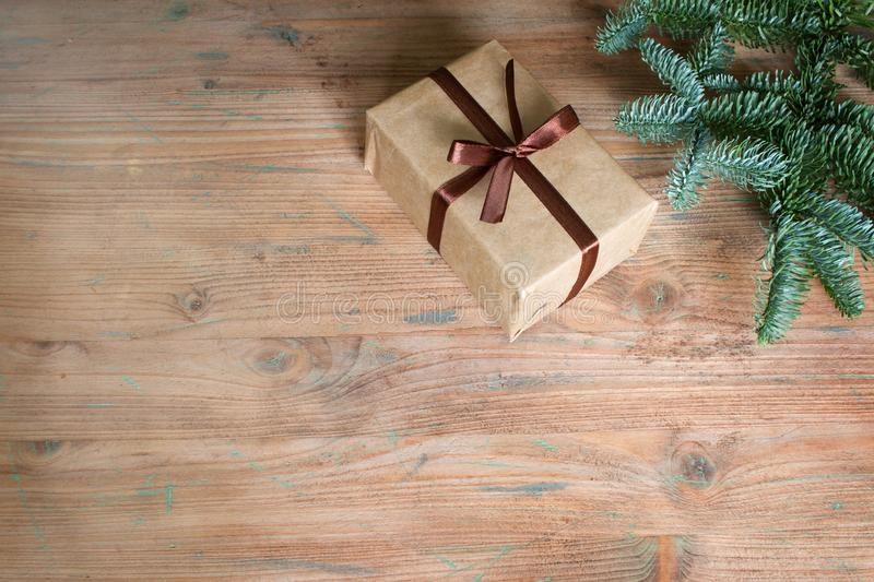 Simple christmas gift box and fir tree on empty wooden background. With free space stock photos