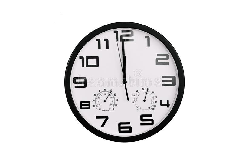 Simple classic black and white round wall clock isolated on white. Clock with arabic numerals on wall shows 12:00.  stock images