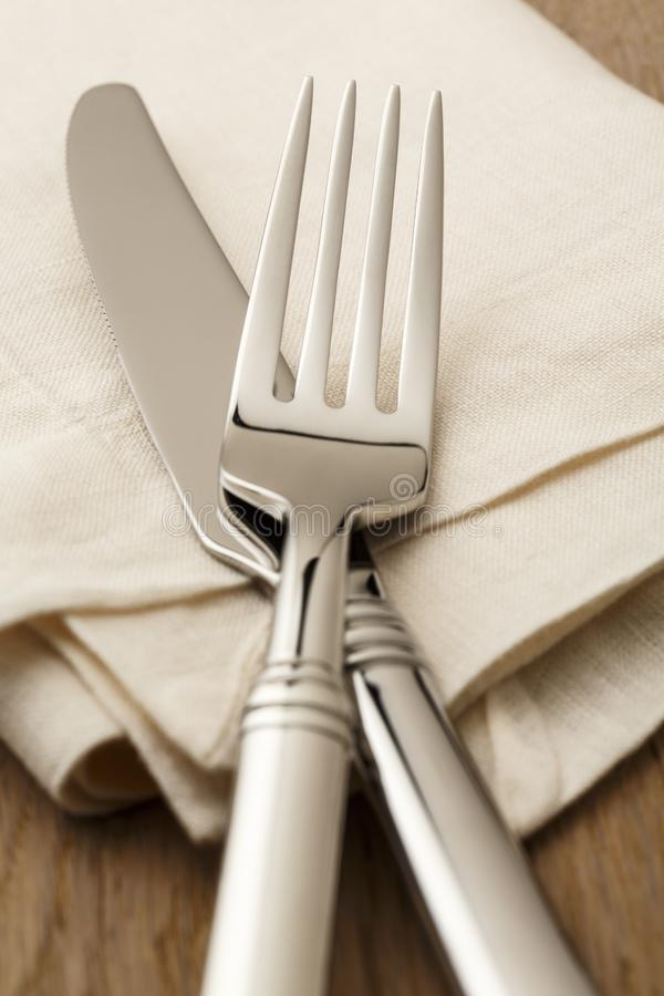 Simple, classic table setting place setting with high quality silverware fork and knife on white linen napkin. Selective focus on. High quality fork and knife royalty free stock photo