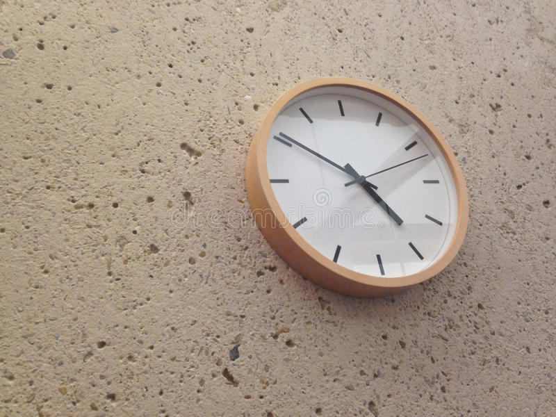 Simple classical analog wall clock. On stone wall. The time is nearly approaching 5pm stock image