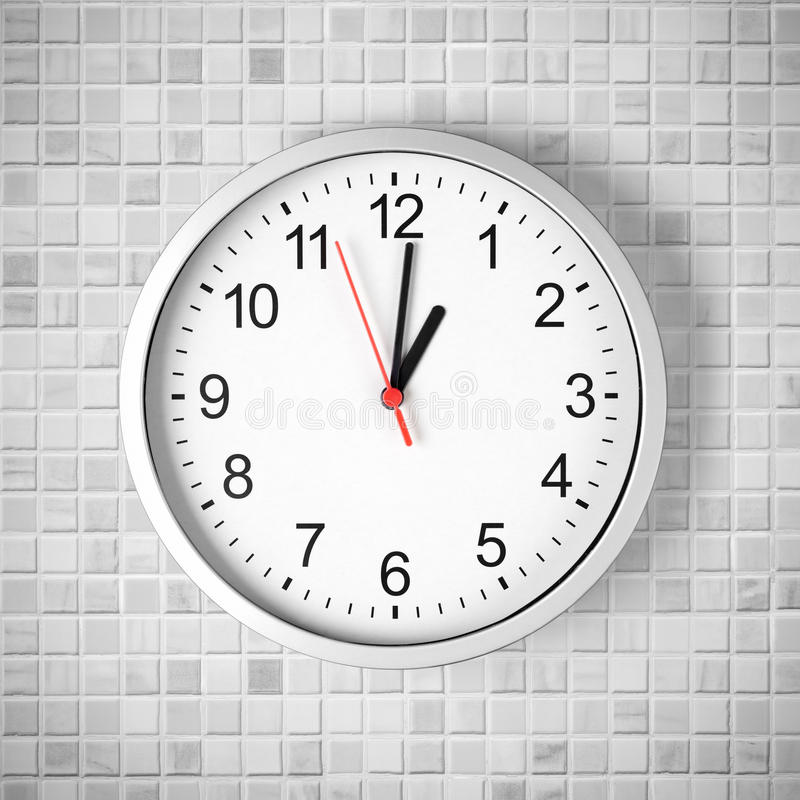 Simple clock or watch on white tile wall stock photography