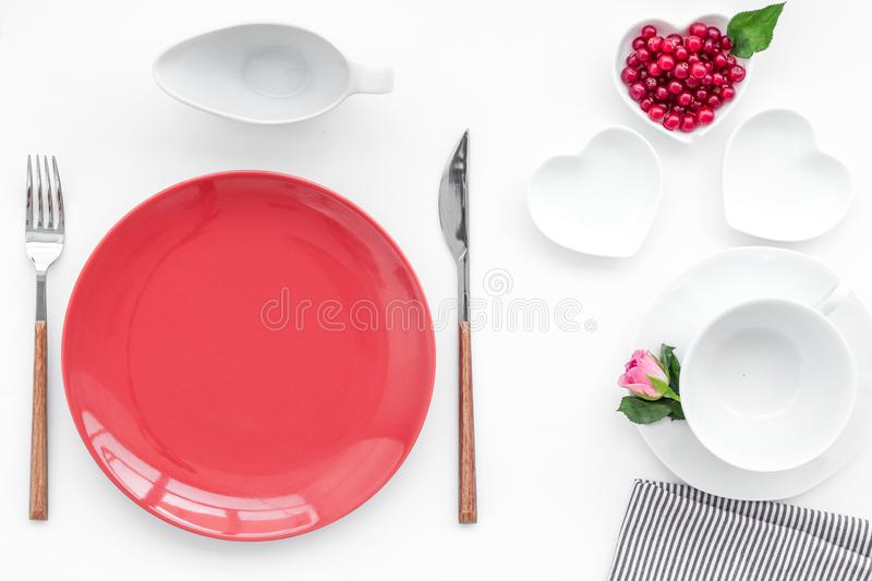 Simple color table setting for celebration with roses, wineberry, red plates and heart-shaped saucers on white table stock photo