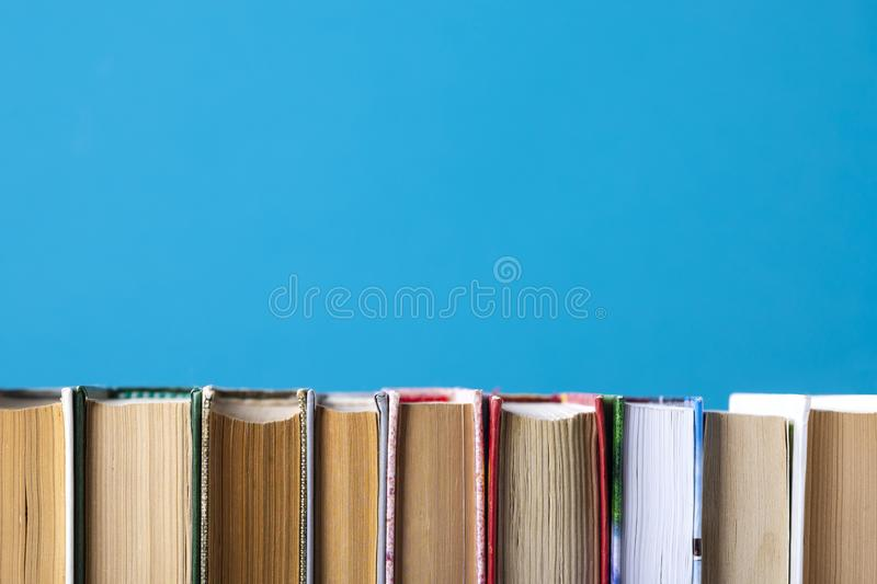 Simple composition of hardback books, raw books on wooden deck table and blue background. Stacking books without inscriptions,. Empty spine. Back to school royalty free stock photo