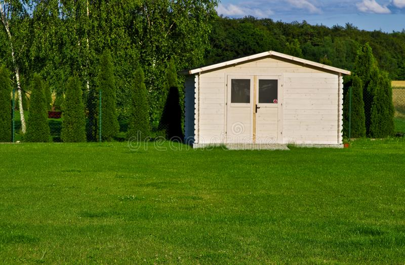 New garden house or shed in green lawn or grass royalty free stock image