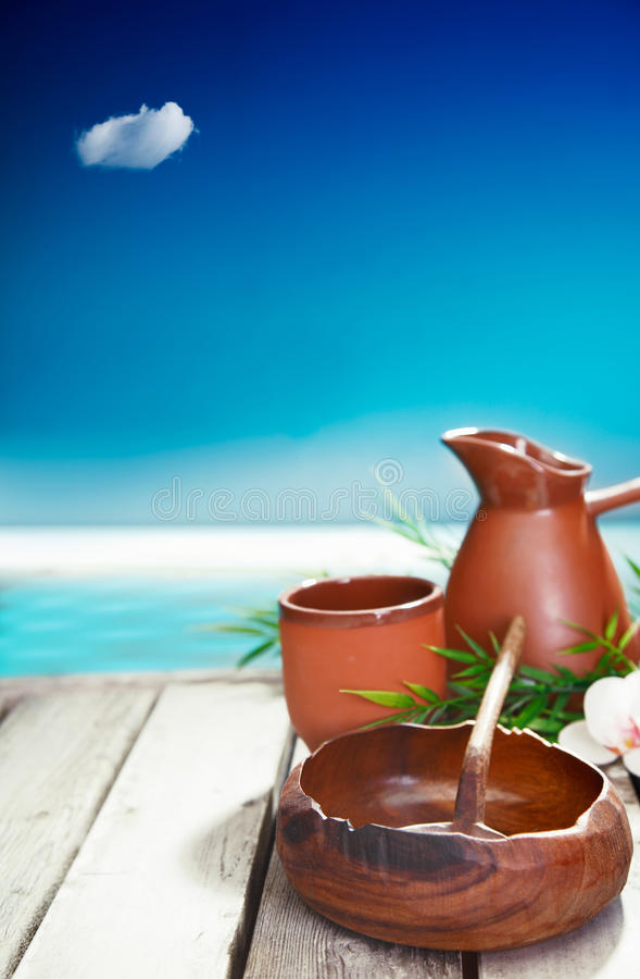 Simple cultural luxuries of travel. Earthenware mug and jug and small wooden bowl represent the simple cultural luxuries of traveling in tropical islands where stock photo