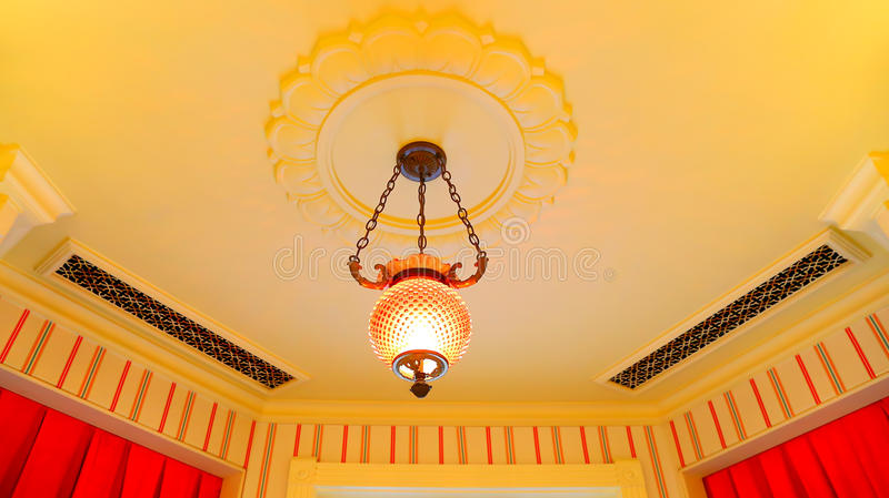 Simple cystal light fixture on ceiling. Elegant crystal light fixture hanging from the decorative ceiling stock photos