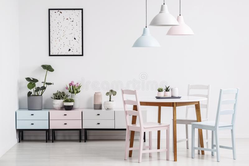 Simple dining room interior with a table, chairs, lamps, poster. And shelves with plants. Real photo concept stock images