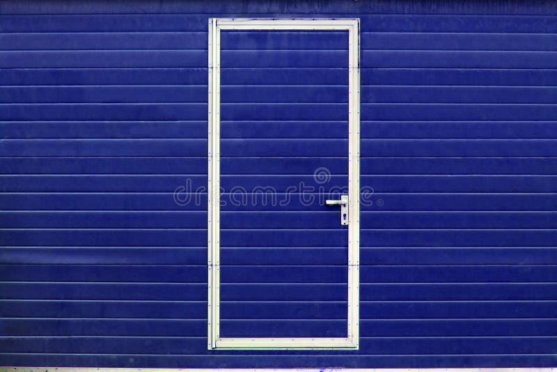 Simple door in blue wall stock image