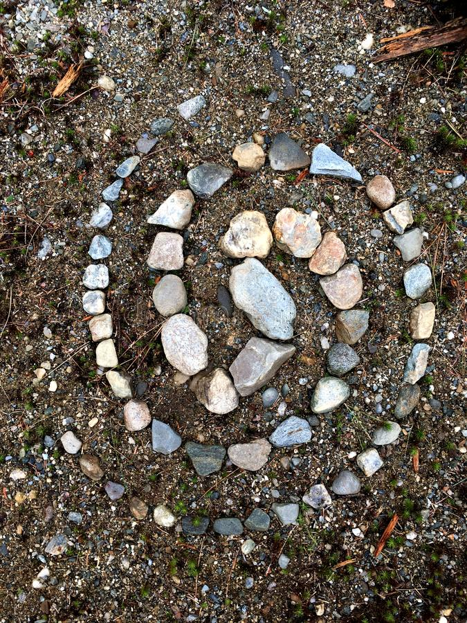 Stone Mandala Pattern Double Spiral. A simple double helix style of natural primitive art with stones making a striking symbolic mandala showing a spiraling stock photo