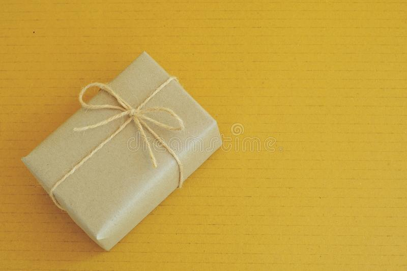 Simple eco friendly gift boxes package wrap with brown paper in old wooden table background, green present concept royalty free stock images