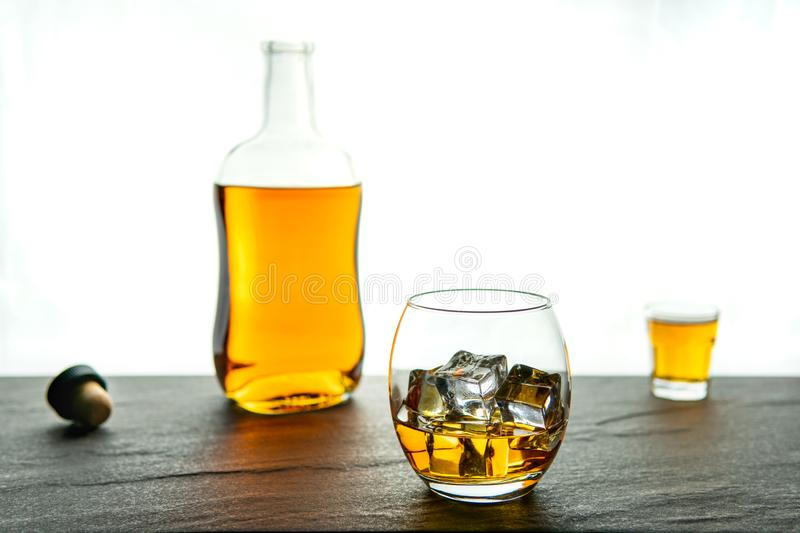 A simple and elegant whiskey whisky bottle, shot and glass with ice on a dark stone base with a white background. With copy space stock photo