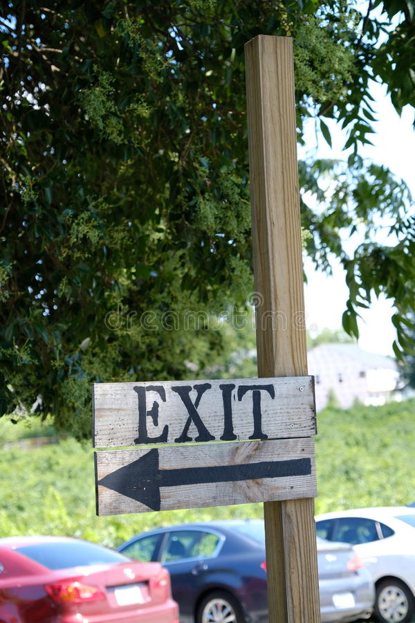 Simple exit sign. Simple wooden rustic antique exit sign in a parking lot royalty free stock photo