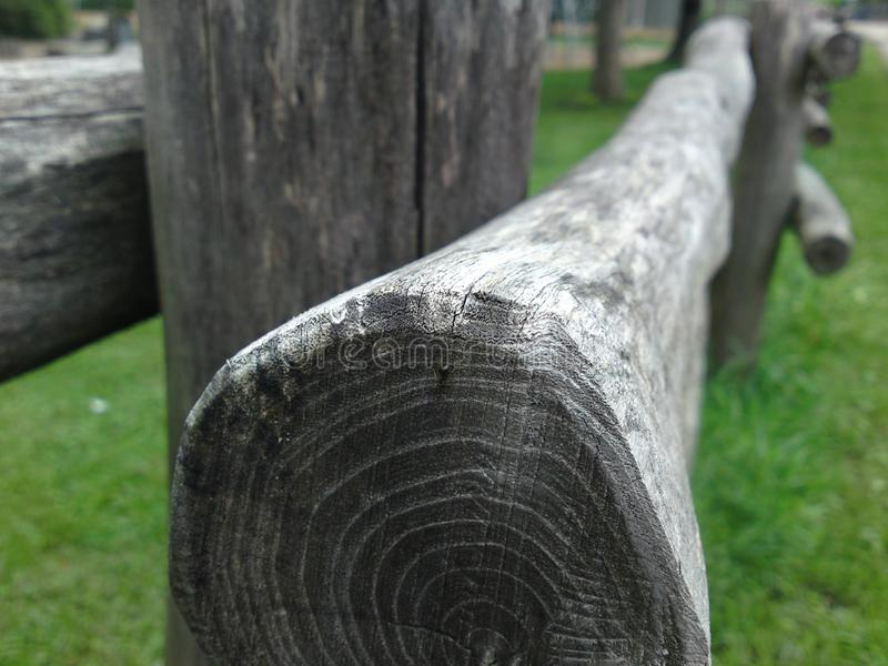 Round wooden beams as a coupling fence. Simple fence made of wooden beams, Round wooden poles as an agricultural fence, Round wood with visible wood grain royalty free stock photography