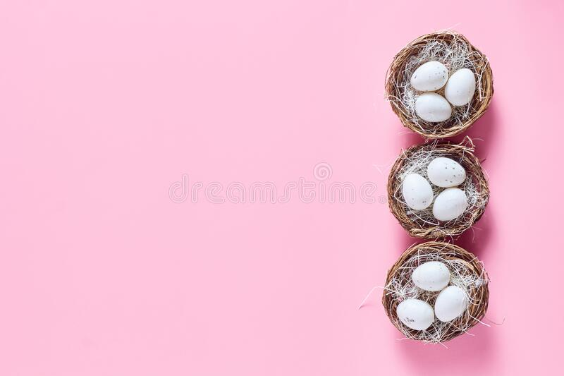 Simple flat minimalistic composition on a pink background. Easter concept. Decorative nest with eggs, space for a text royalty free stock photography