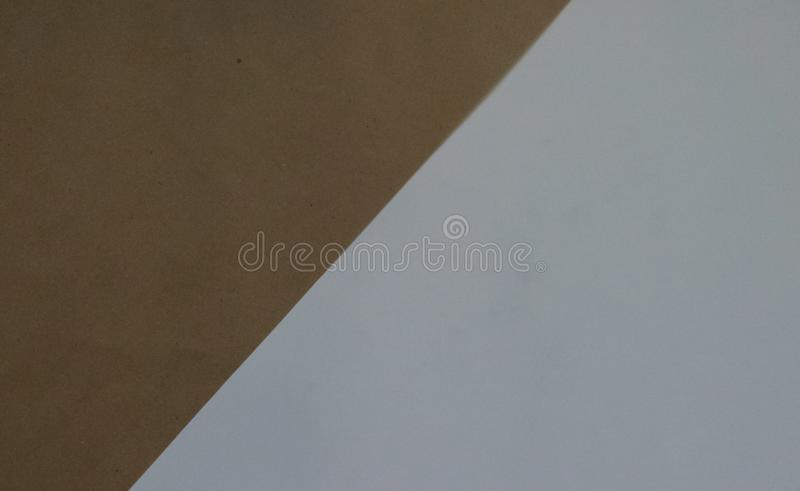 Simple geometric background of white backdrop and Kraft brown paper. The top view. Close-up.  royalty free illustration