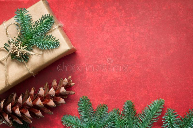 Simple gifts and fir tree christmas ornament decoration on empty red background. Closeup stock photos