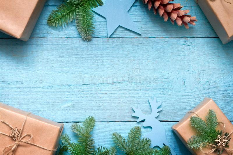 Simple gifts and fir tree christmas ornament decoration on wooden empty blue old background planks. Closeup stock images