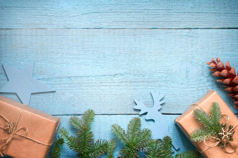 Simple gifts and fir tree christmas ornament decoration on wooden empty blue old background planks. Closeup stock photo