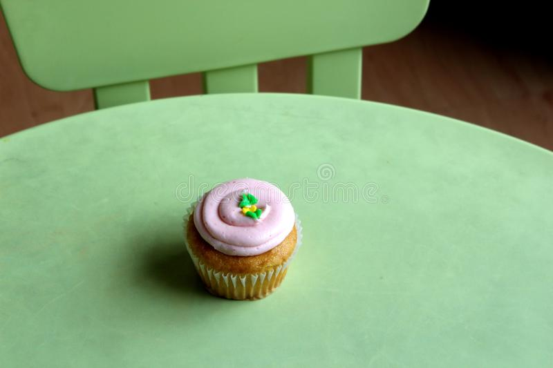 Simple green table and chair with one strawberry cupcake with thick, creamy frosting stock image