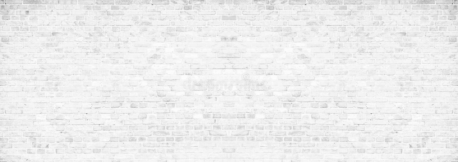 Simple grungy white brick wall with light gray shades pattern surface texture background in wide panorama banner format stock photo