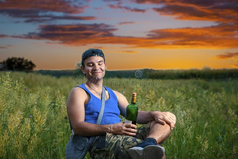 Simple guy in a cap enjoys nature and silence with a bottle of wine, with eyes closed,in the background is a beautiful summer royalty free stock image