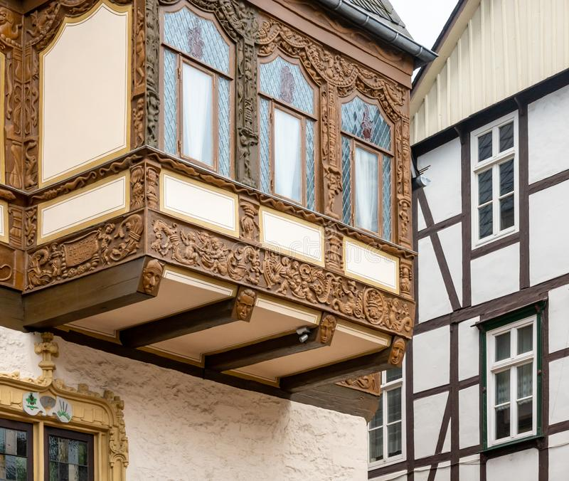 Simple half-timbered façade in the background and richly carved half-timbered house on an oriel in the old town.  royalty free stock images