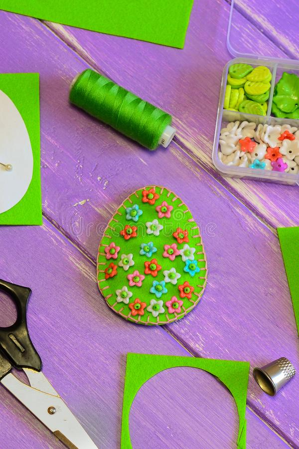Pretty green Easter egg decoration with bright floral pattern. Felt egg decoration, scissors, paper template, thread, plastic box royalty free stock photography
