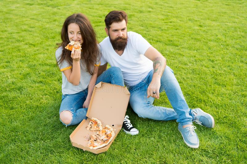 Simple happiness. Cheat meal. Couple eating pizza relaxing on green lawn. Fast food delivery. Bearded man and girlfriend stock images