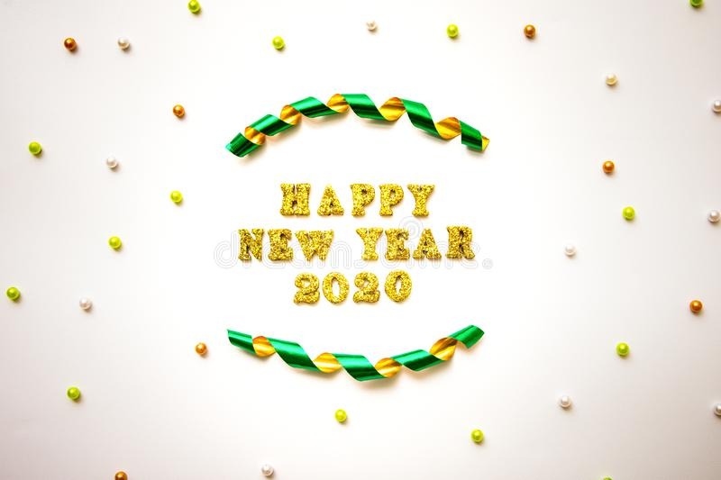 Simple happy new years 2020 text in gold lettering, curled ribbon and colorful beads  isolated on white background stock photography