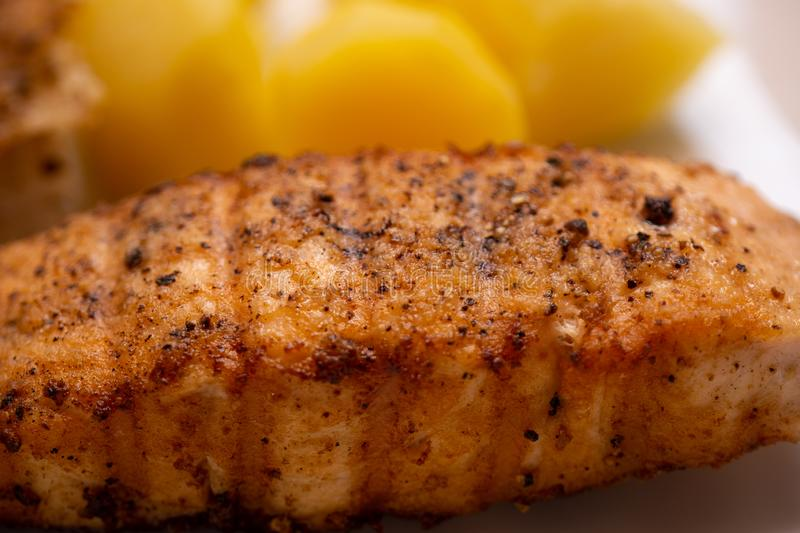 Simple home cooking for bachelors from a marinated grilled filet of haddock and boiled potatoes, yellow boiled potatoes in the royalty free stock image